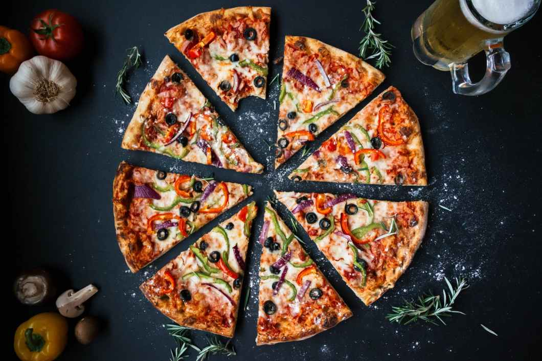 baked pizza on top of black surface near filled glass tankard