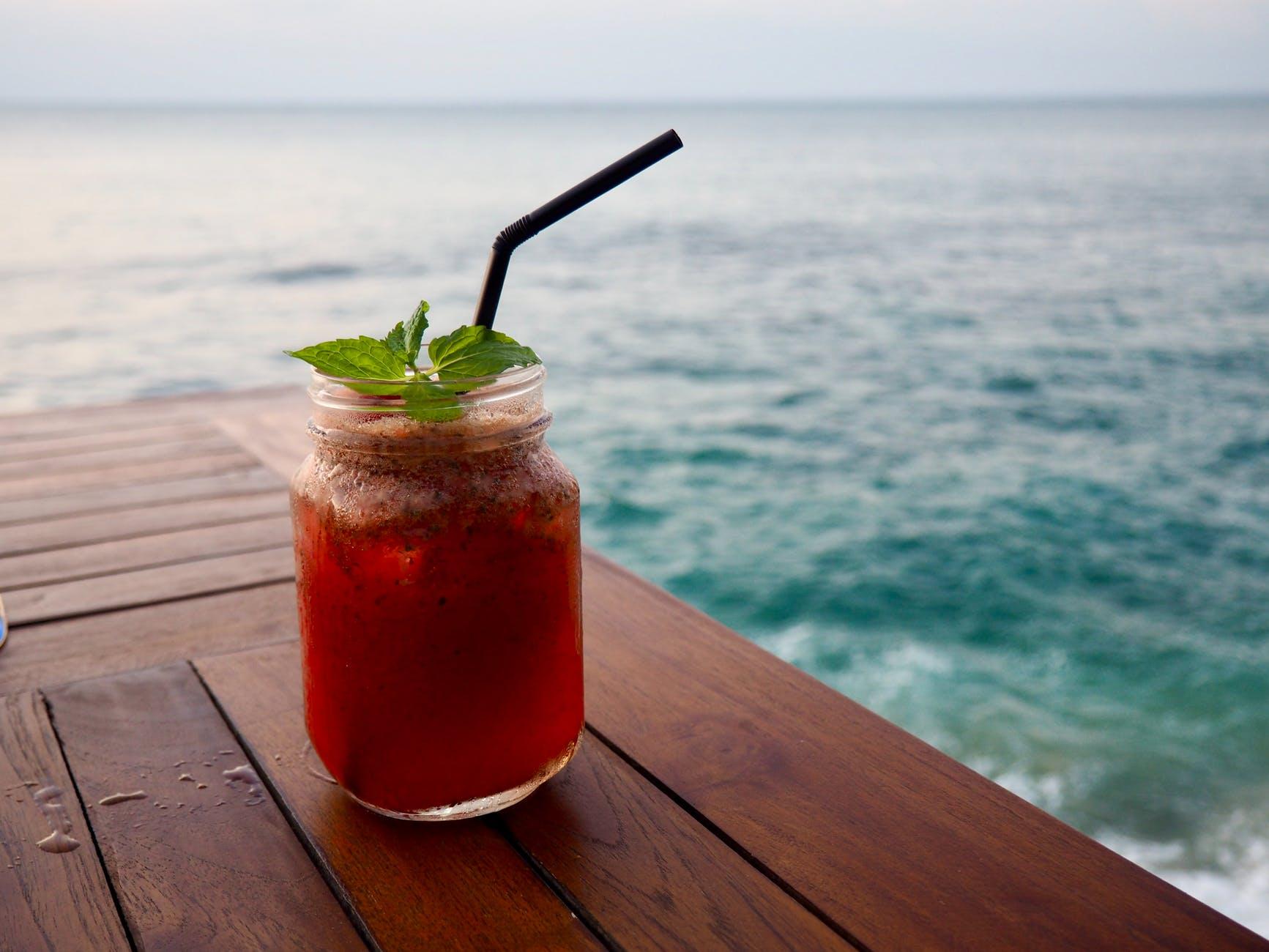 photo of orange beverage in clear glass mason jar