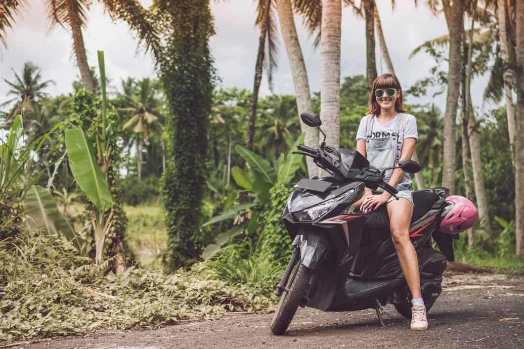 woman in gray shirt riding black motor scooter