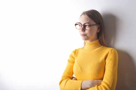 woman standing against wall wearing yellow turtleneck sweater