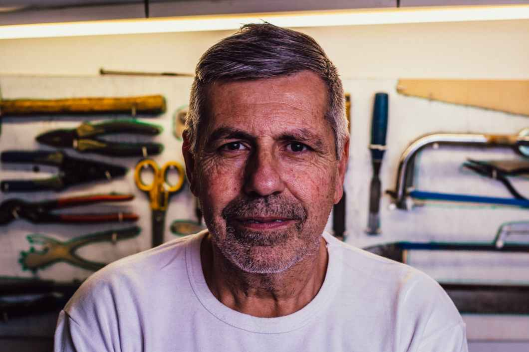 portrait photo of man in white crew neck t shirt with assorted hand tools in background