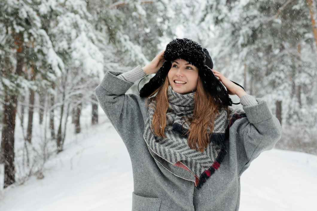 smiling woman standing beside trees covered by snow