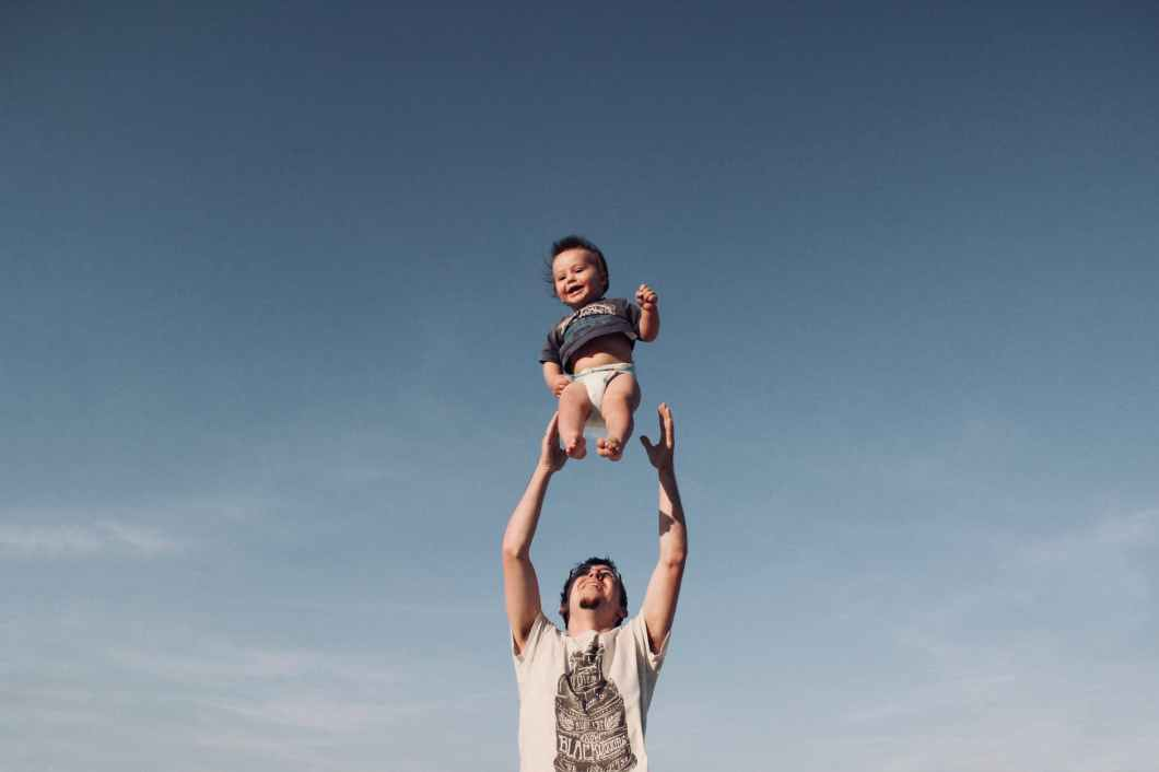 photo of man in raising baby under blue sky