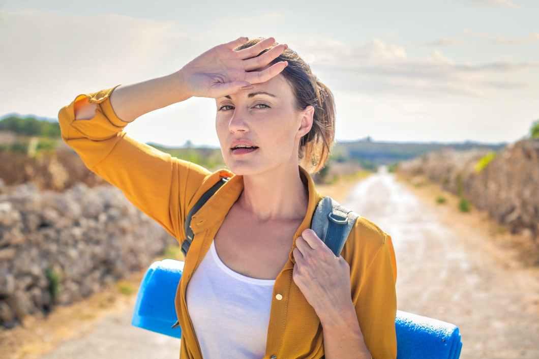 woman in yellow long sleeve carrying blue yoga mat
